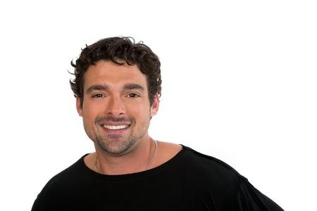 viso di uomo: Giovane attraente, con i capelli scuri e ondulati sorride alla fotocamera. Isolato su sfondo bianco con spazio per il testo.
