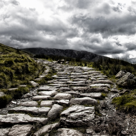 Dramatic depiction of the dry stone hikers path leading to the summit of Mount Snowdon, under a stormy sky, Snowdonia, North Wales   photo