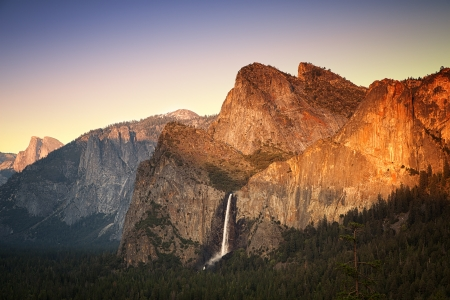 Yosemite at sunset as seen from the Tunnel View viewing point, showing the Half Dome, Cathedral Rocks and the Bridalveil Falls being lit by the setting sun  Yosemite National Park, California, USA photo