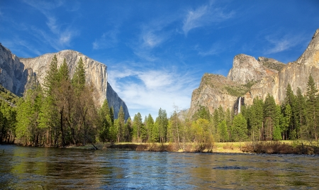 Yosemite Valley panorama showing the El Capitan, the Cathedral Rocks and the Bridalveil Falls,  with the Merced river in the foreground and blue sky with wispy clouds in the background.  photo