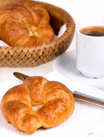 Fresh continental breakfast of croissant and coffee photo