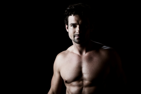 physique: Low key portrait over black of an athletic young man with torso, looking directly to the camera  Stock Photo