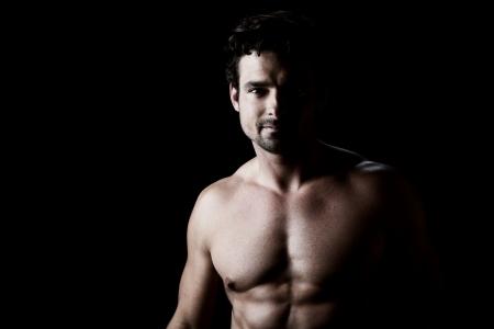 hombre sin camisa: Retrato oscuro sobre negro de un hombre joven con el torso atl?tico, mirando directamente a la c?mara