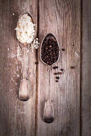 tarnished: Vintage effect image of tarnished silver spoons filled with salt crystals and black peppercorns, over rough wood background