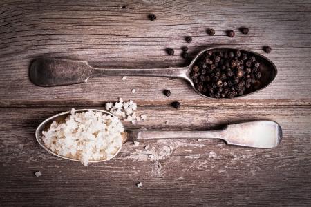 거친 나무 배경 위에 소금 결정과 검은 후추, 가득 tarnished 실버 스푼의 빈티지 효과 이미지
