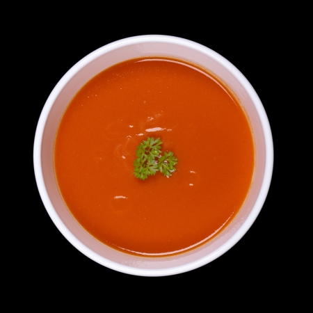 gaspacho: A bowl of tomato soup with a parsley garnish, isolated on black background