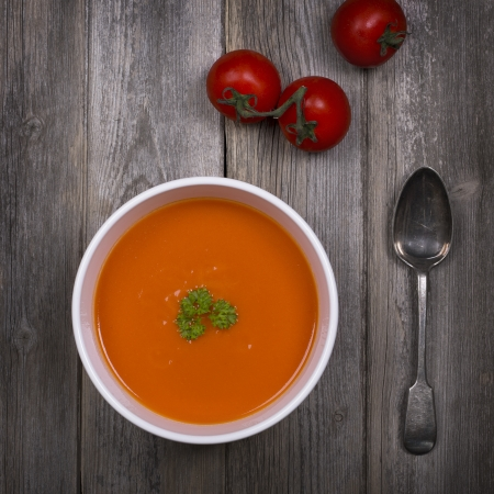 A bowl of tomato soup with a tarnished silver spoon and fresh vine tomatoes, against a rustic wood tabletop  Vintage style with intentional vignette and selective desaturation