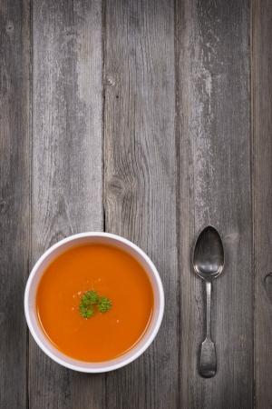 Een kom tomatensoep met een bezoedelde zilveren lepel, tegen een rustieke houten tafel vintage stijl met opzettelijke vignet en selectieve desaturatie en ruimte voor uw tekst