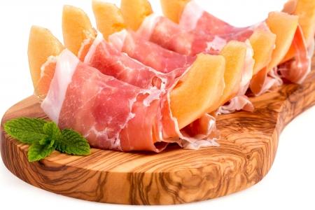 Jamón de Parma y melón en rodajas de arranque sirve en tablero de madera de oliva sobre blanco