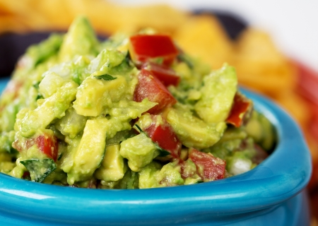 nacho chip: Closeup of a bowl of fresh guacamole with corn tortilla chips  Intentional shallow depth of field  Stock Photo