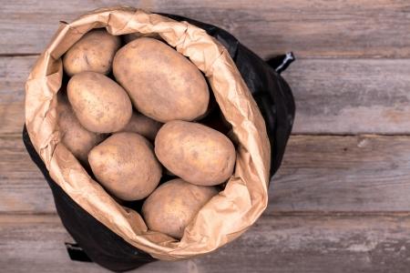 unwashed: Potateos sporchi in un sacchetto di carta marrone e nero, su sfondo di legno