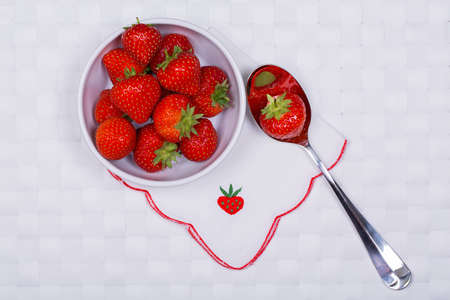 Bowl of whole ripe strawberries on white tablecloth with strawberry embroidered napkin and silver spoon photo