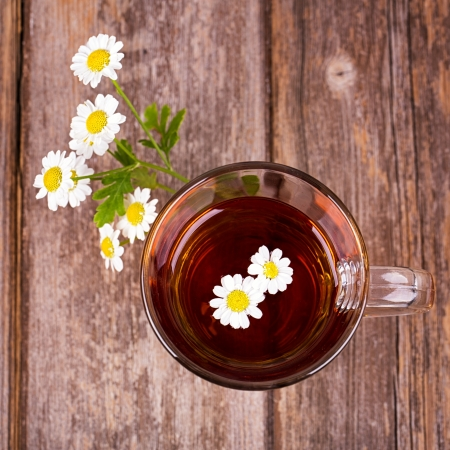 chamomile tea: Glass cup of camomile tea with camomile flowers, on vintage wood table.