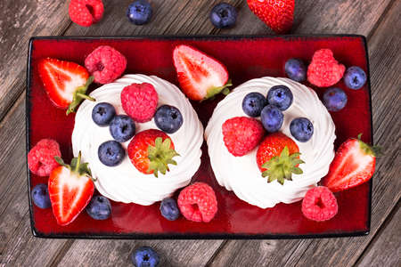 Summer fruit platter of strawberry, raspberry, blueberry and meringue with cream, on red ceramic platter on old wood table. Stock Photo - 21806861