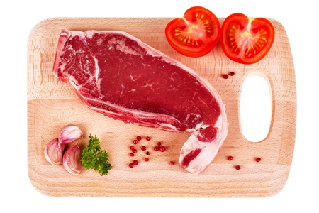 Bone in sirloin steak with garlic, parsley, pink peppercorns and sliced tomato on wood chopping board, isolated over white background photo