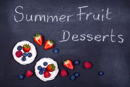 Summer fruit pavlova desserts with fresh berries, over a chalkboard photo