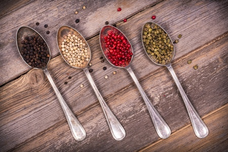 Tarnished silver spoons containing black, white, pink and green peppercorns over old wood background  Vintage style processing  Stock Photo - 21807034