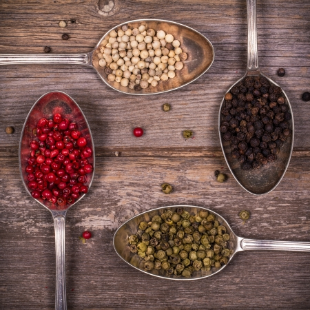 peppercorns: Tarnished silver spoons containing black, white, pink and green peppercorns over old wood background  Vintage style processing