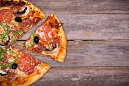 Pepperoni pizza with sliced vegetables on rustic wood background