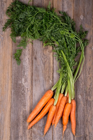A bunch of fresh carrots on vintage style wood background photo