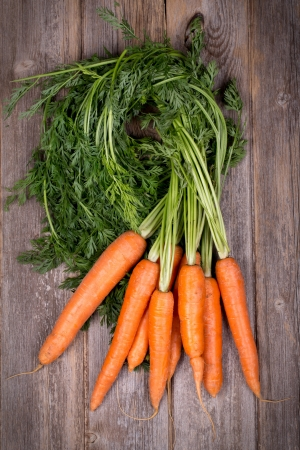 A bunch of fresh carrots on vintage style wood background Archivio Fotografico