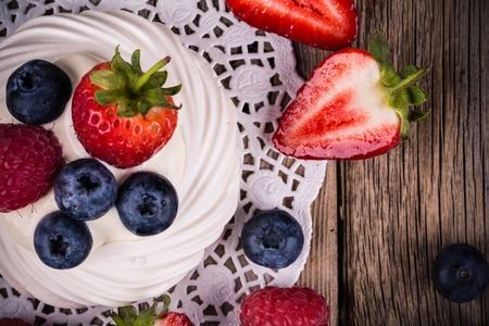 Summer fruit pavlova closeup, over vintage style wood background  photo