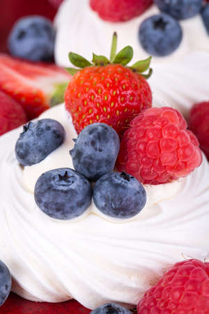 Closeup of summer fruit pavlovas with strawberries, raspberries and blueberries  photo