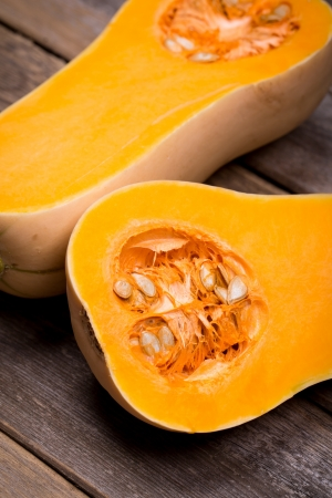Sliced butternut squash over old wood background with intentional vignette Stock Photo