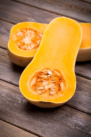 pumpkin seed: Sliced butternut squash over old wood background with intentional vignette Stock Photo
