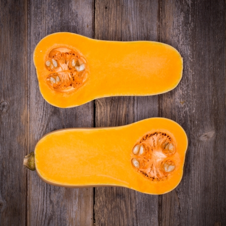 Sliced butternut squash over old wood background with intentional vignette Archivio Fotografico