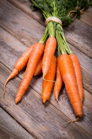 zanahoria: Manojo de zanahorias frescas sobre fondo de madera de la vendimia Foto de archivo