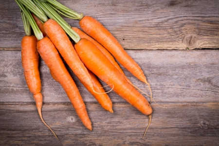 Bunch of fresh carrots over vintage wood background  photo