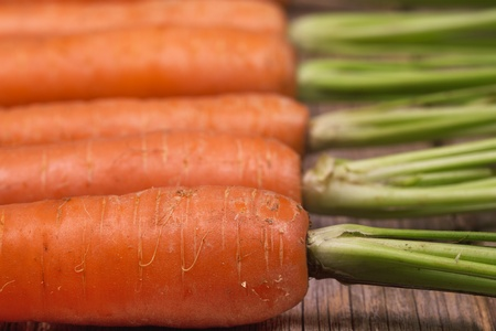 pulled over: Closeup of a row of freshly pulled carrots over an old wood background Stock Photo