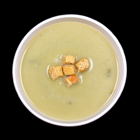 potato soup: A bowl of leek and potato soup with a bread crouton garnish, isolated on black background