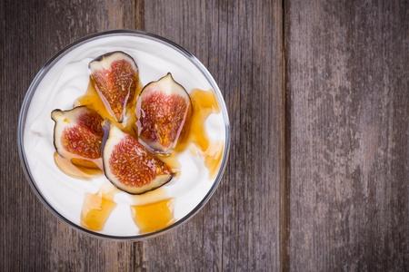 yogurt natural: Yogur griego con higos y miel, en un recipiente de vidrio sobre fondo de madera vieja Foto de archivo