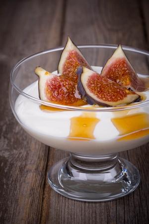 greek pot: Yogurt greco con fichi e miele, in una ciotola di vetro su sfondo di legno vecchio