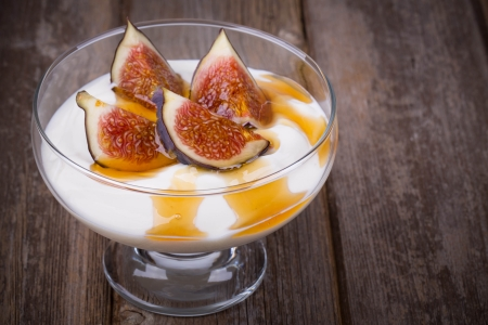 yaourt: Yaourt grec aux figues et miel dans un bol en verre sur fond de vieux bois