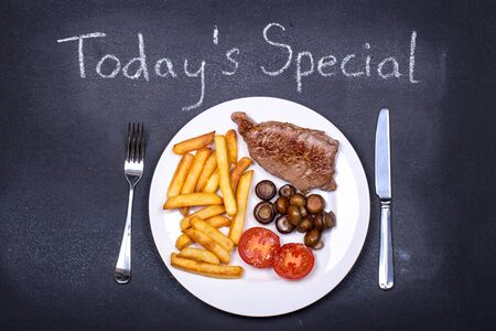 Steak and chips dinner on a chalkboard as the dish of the day  photo