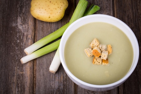 potato soup: A bowl of leek and potato soup with bread croutons, over old wood table with fresh leeks and potatoes alongside