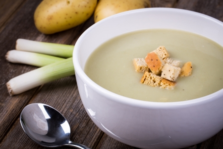 leek: A bowl of leek and potato soup with bread croutons, over old wood table with fresh leeks and potatoes alongside