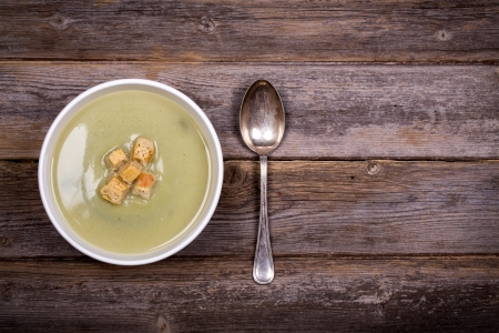 A bowl of leek and potato soup with bread croutons, over old wood table