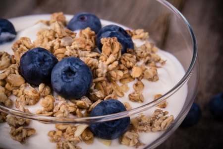 Yogurt with granola and fresh blueberries, in glass bowl over old wood background. Vintage effect. 写真素材