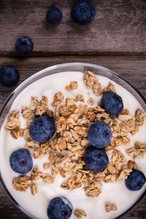 Yogurt with granola and fresh blueberries, in glass bowl over old wood background. Vintage effect. photo
