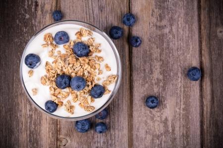 Yoghurt met muesli en verse bosbessen, in glazen kom over oude houten achtergrond. Vintage effect.