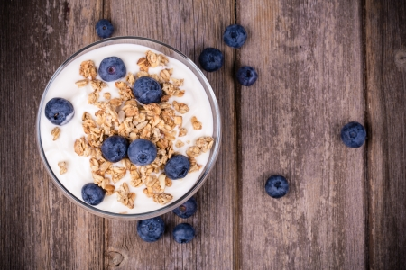 Yogurt with granola and fresh blueberries, in glass bowl over old wood background. Vintage effect. Imagens