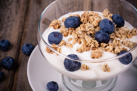 yogurt natural: Yogurt con arándanos granola y fresca, en un tazón de cristal sobre fondo de madera vieja. Efecto vintage.