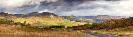 Dramatic sky over the glen with road running through. Scottish Highlands, UK photo