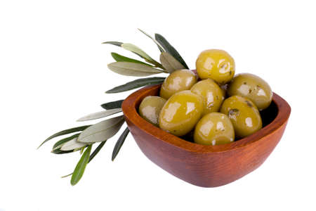Green olives in a wooden bowl with olive branch. Isolated on white photo