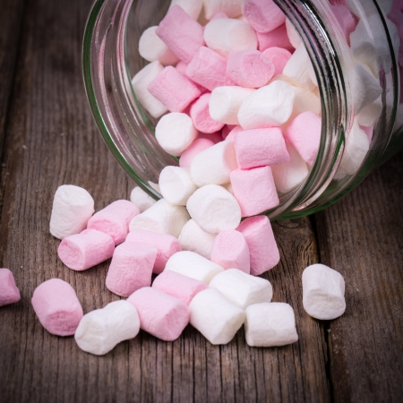 Pink and white marshmallows spilling from a storage jar, over old wood background. Vintage effect with intentional vignette 스톡 콘텐츠