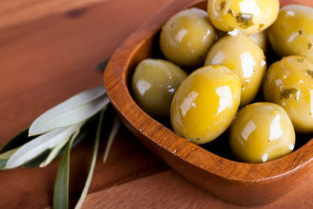 Green olives in a wooden bowl with olive branch, on wooden background. Stock Photo - 22928099